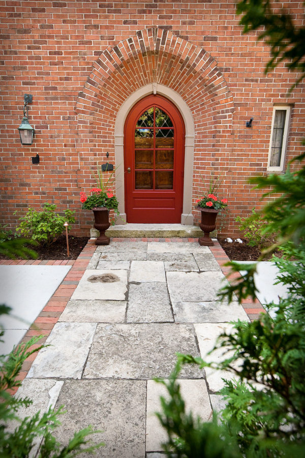 a charming arc red door with large glass panes and brick wall exterior for a historical ambiance