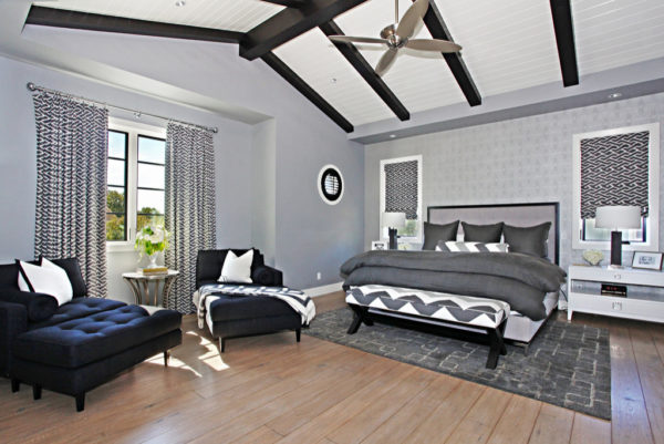 a trendy bedroom design featuring wood flooring, grey walls, and various black accents