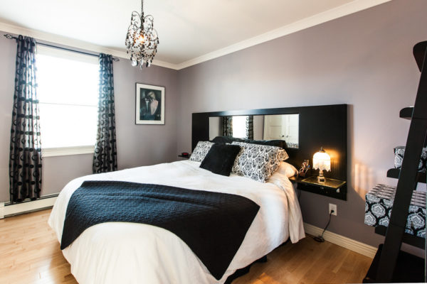 building mirrors into the black headboard to create the illusion of space in an apartment style bedroom