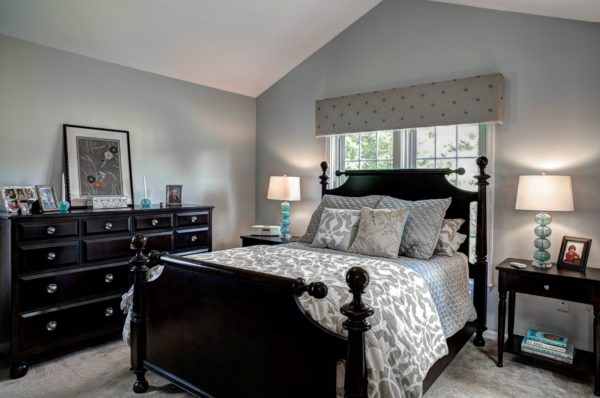 evoke the classic cottage house coziness in this grey bedroom with traditional black furniture