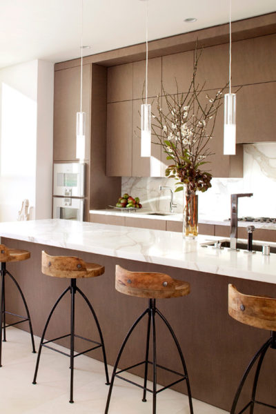 pair brown cabinetry with white marble countertops and flooring for a trendy galley kitchen