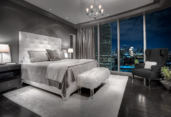 this lavish bedroom with grey walls, grey bedding, and polished black flooring
