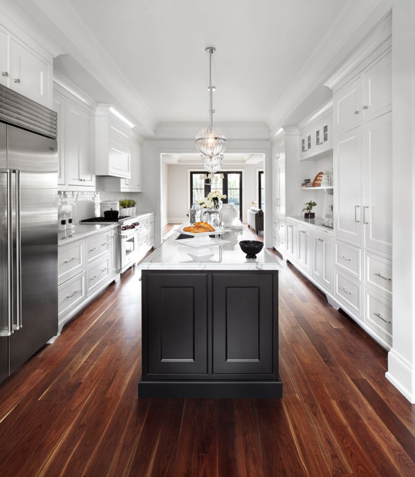 use brown wood flooring to sweeten a large contemporary kitchen with white walls and cabinetry