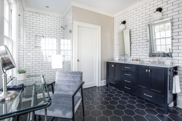 add a glass table vanity in addition to the subway tile with black grout shower walls and honeycomb tile bathroom floors