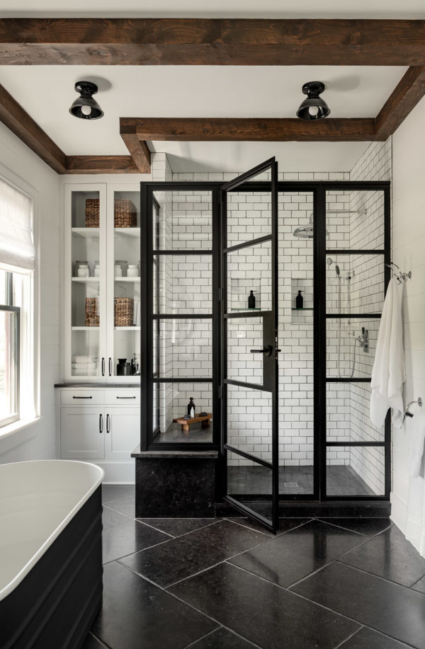introduce wooden ceiling beams to enhance a cottage bathroom featuring subway tile with black grout walls