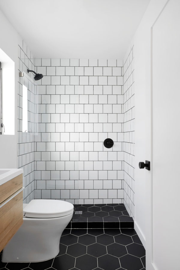 pair subway tile with black grout walls and black honeycomb tile floors for a modern bathroom