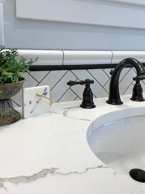 subway tile with black grout makes a dynamic bathroom backsplash against black faucets