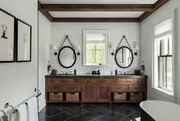 this farmhouse bathroom has a modern subway tile with black grout backsplash and rustic wood elements
