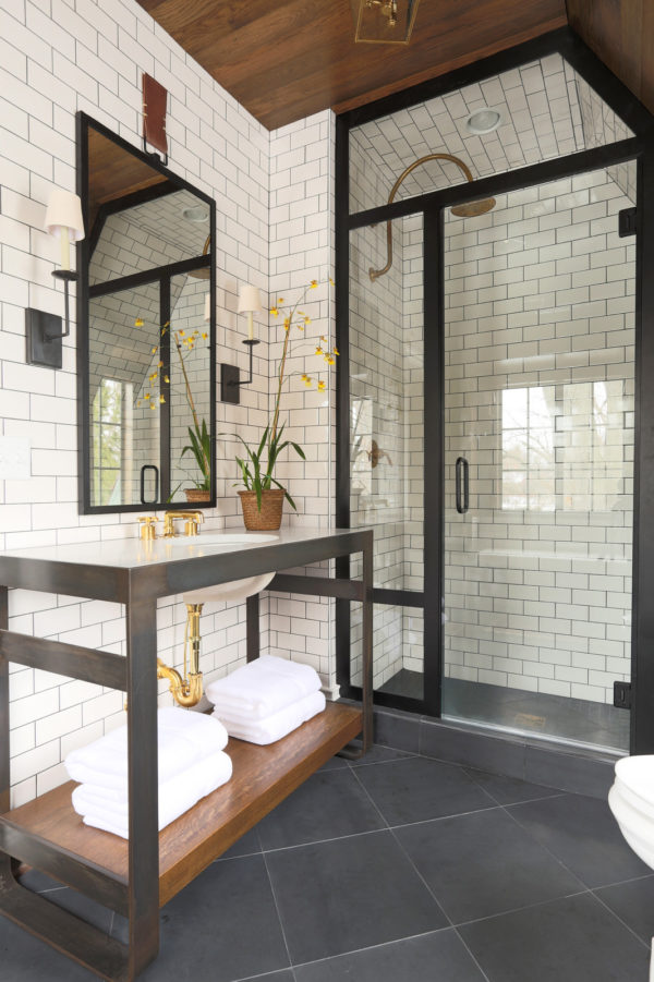 use black accents and medium tone wood to complement subway tile with black grout walls