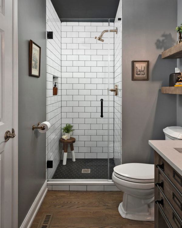 wood flooring and grey walls to contrast subway tile with black grout in a cozy bathroom